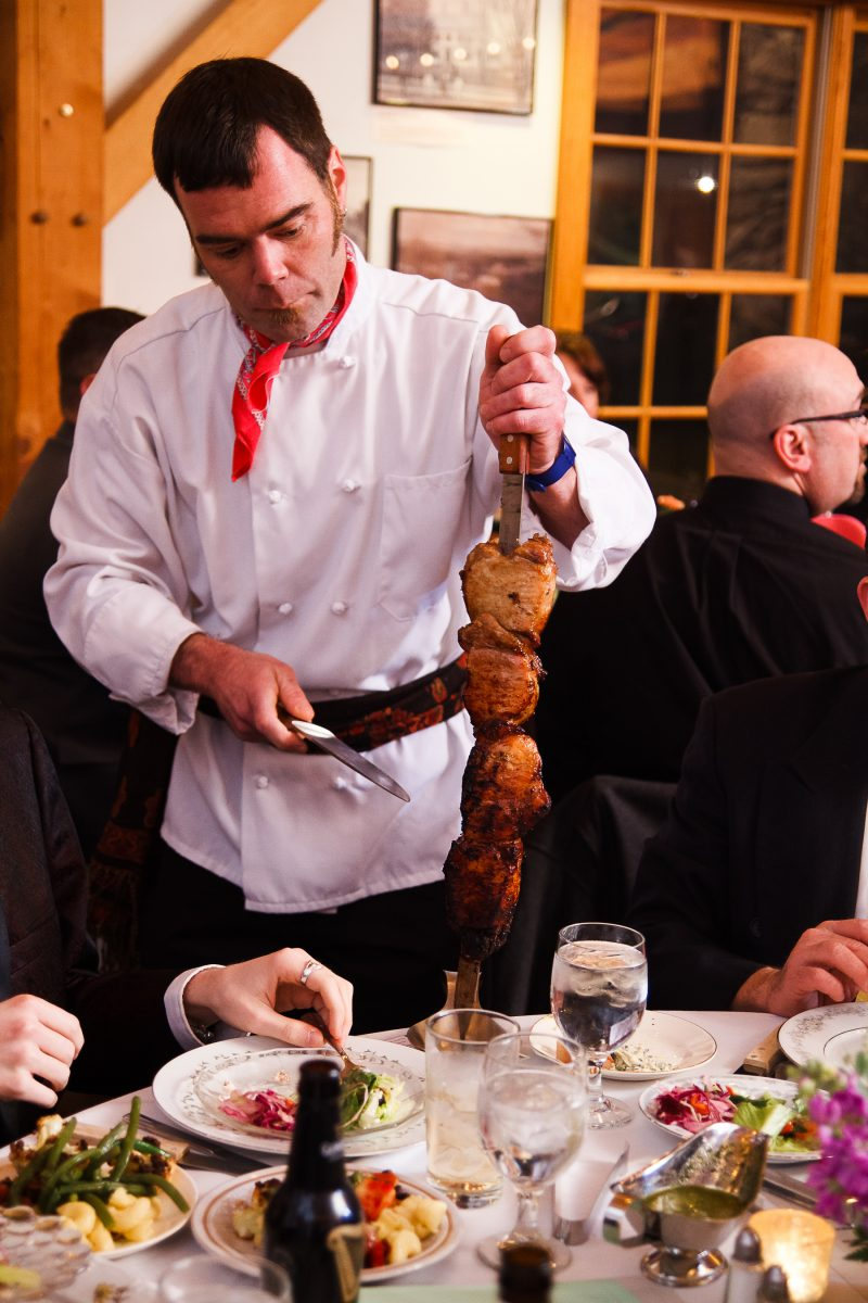 A chef prepares freshly cooked meat for a guest's plate