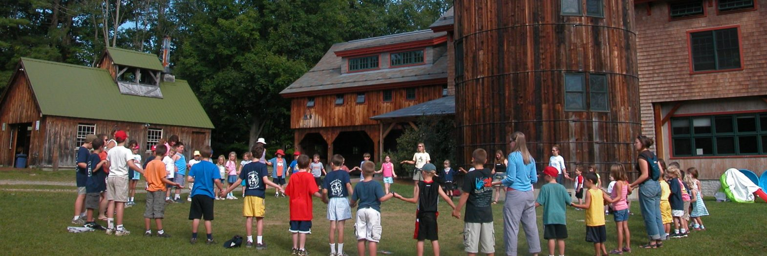A kids camp circle with a barn and silo in the background