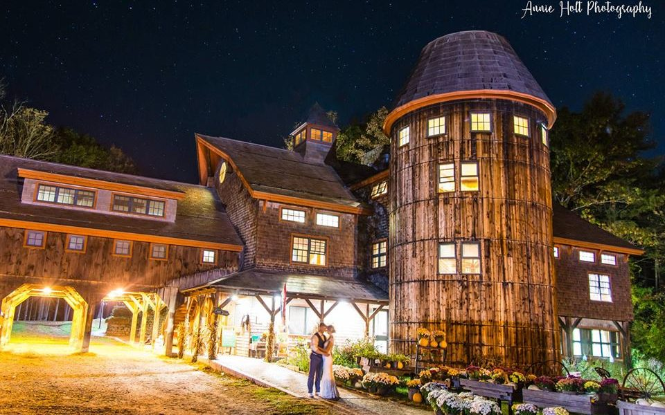 a bride and groom posing in front of Stonewall farm silo, at night in the fall