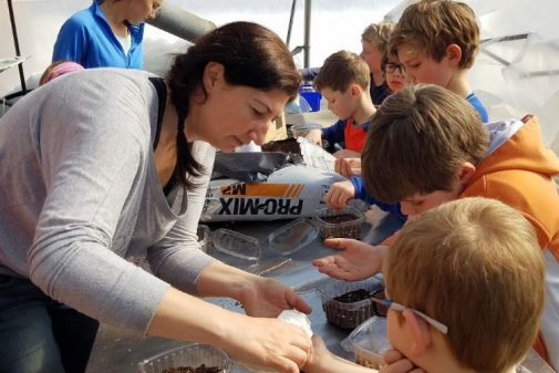 kids planting seeds in greenhouse
