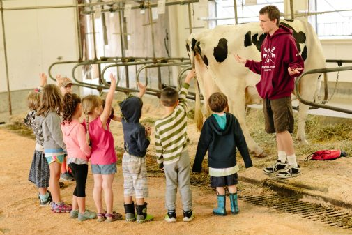 a group of kids standing in a milking barn with hands raised for questions