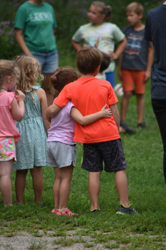 Two kids at camp with one arm around each other being supportive