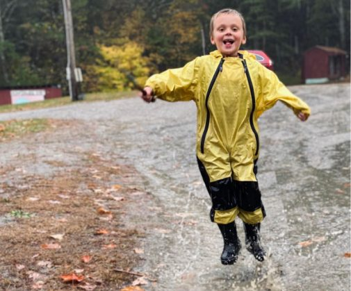 Boy enjoying being outside in the rain.