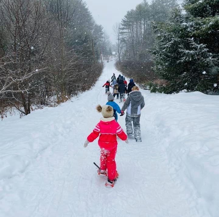 A group of kids snowshoe up a long plath as it lightly snows