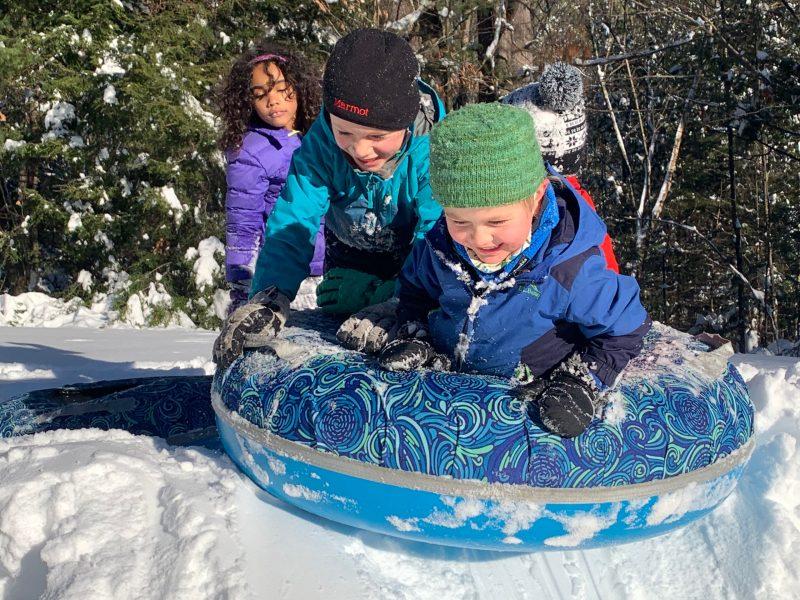 kids enjoying sliding in the snow at stonewall farm.