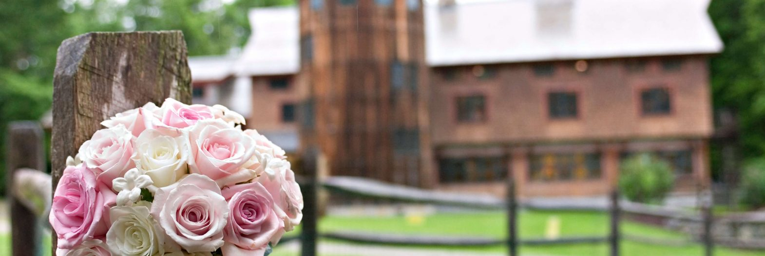 a bridal bouquet of pink and white roses, rests on a post and beam fence