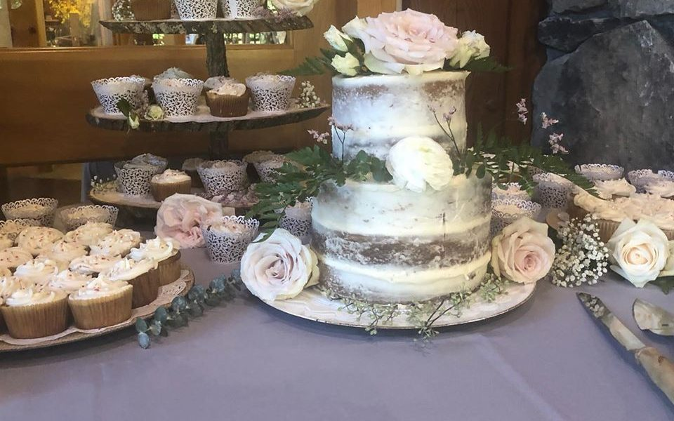 A rustic looking wedding cake surrounded by cupcakes and flowers