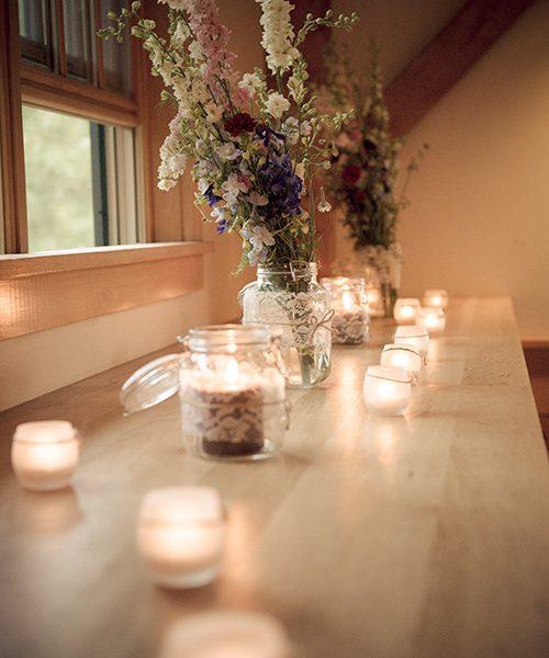 a window bench with mason jars and tealights