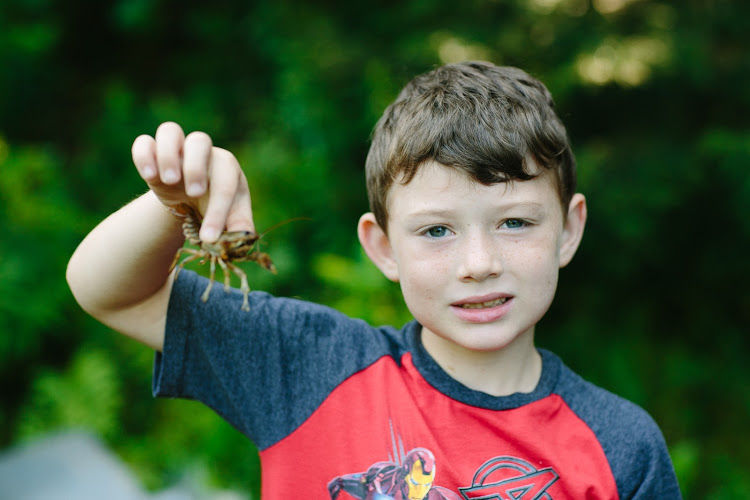 boy holding crawfish