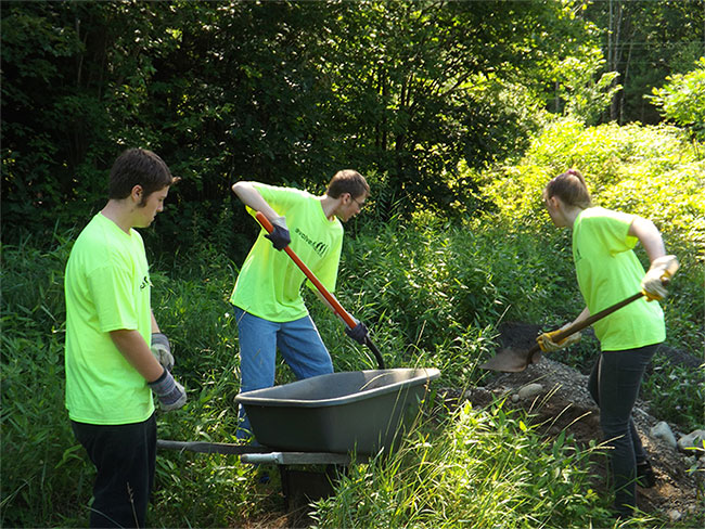 Three Young Adults in matching neon shirts working with some gravel.